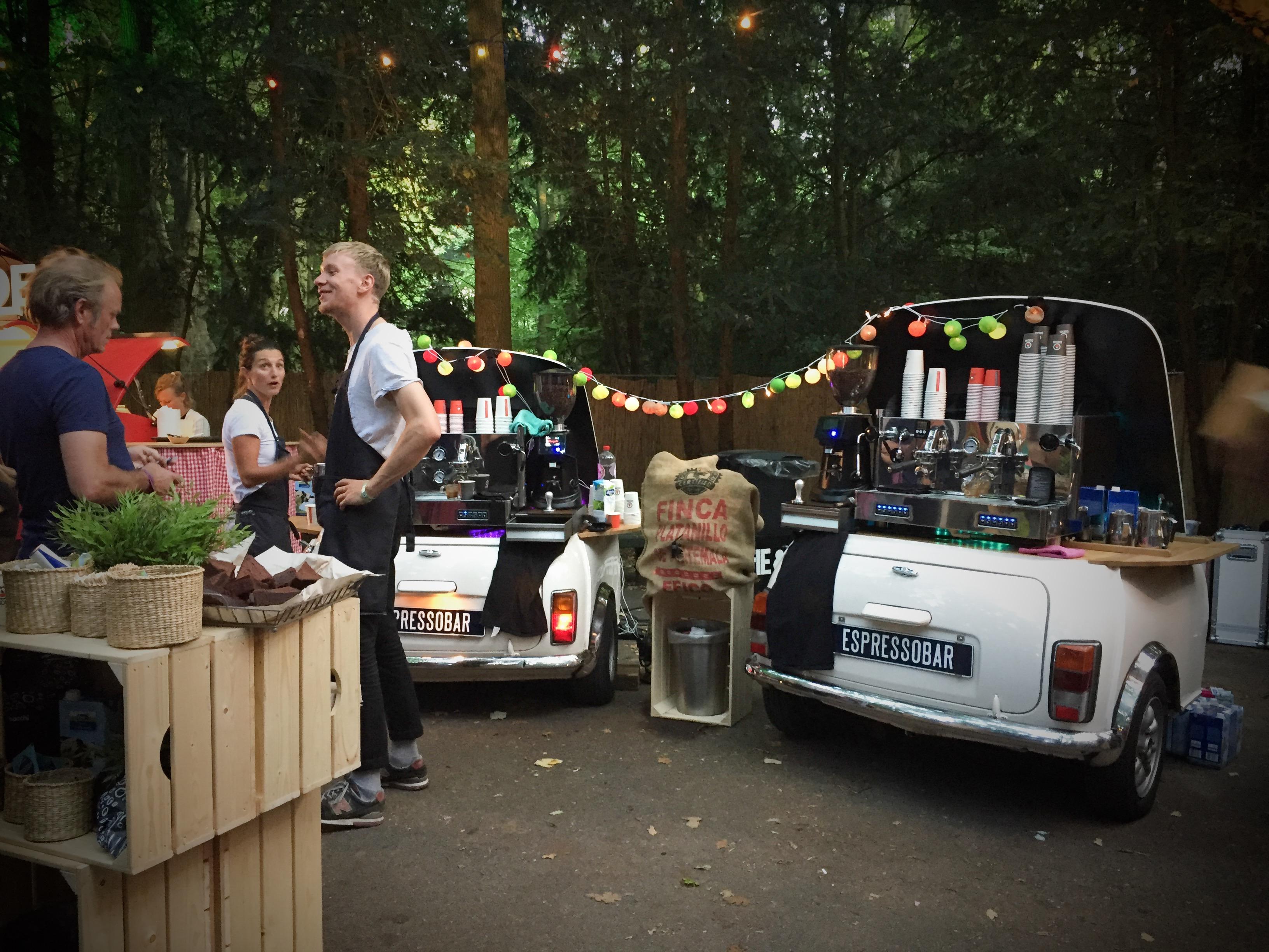 Een tweetal espressobars met een barista op een festival