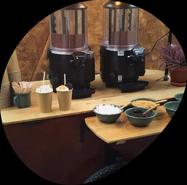 Warme chocolademelk machines met ingrediënten ervoor op een houten tafel